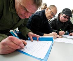 Mitarbeiter des Druck- und Verlagshauses der Frankfurter Rundschau (FR) ihre E-Mail-Adressen in Listen ein, um in Kontakt zu bleiben. Foto: dpa / Nicolas Armer