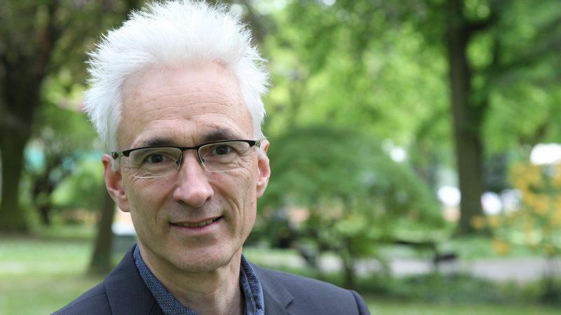 Porträt des Journalisten Harald Gesterkamp vor grünen Bäumen